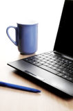 Blue coffee cup and opened lap top. Royalty Free Stock Photo