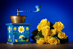 Blue coffee grinder and roses Stock Images