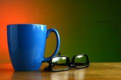 Blue coffee mug and eyeglasses Royalty Free Stock Image