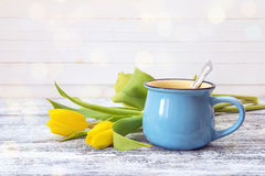 Blue coffee mug with yellow tulips on a white background. Royalty Free Stock Photo