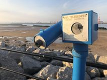 Blue coin-operated telescope. In New Brighton at the seaside, overlooking the River Mersey with rocks, railings and a sandy beach Royalty Free Stock Photos