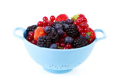 Blue colander with healthy fresh fruit over white background Stock Photography
