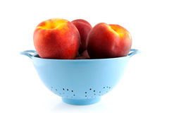 Blue colander with peaches Royalty Free Stock Photography