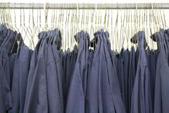Blue collar work shirts uniforms on hangers. This is a shot of blue color work shirts on hangers Royalty Free Stock Photos