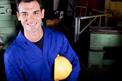 Blue collar worker. Happy blue collar worker portrait in factory royalty free stock photos
