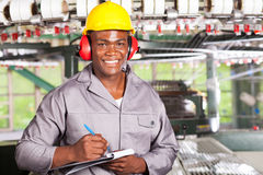 Blue collar worker. Handsome african american blue collar worker portrait inside factory stock images