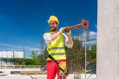 Blue-collar worker carrying a heavy metallic bar during work. Full length of a blue-collar worker wearing safety equipment, while carrying a heavy metallic bar royalty free stock photography