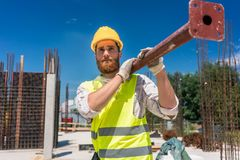 Blue-collar worker carrying a heavy metallic bar during work. Full length of a blue-collar worker, wearing safety equipment while carrying a heavy metallic bar royalty free stock images