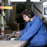 Blue collar worker cleaning machine. Blue collar worker at machine in factory stock photography