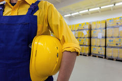 Blue collar worker. Closeup of a blue collar worker holding hard hat stock images