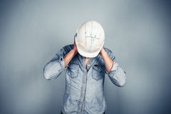 Blue collar worker covering his ears Stock Image