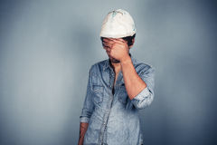 Blue collar worker covering his face Royalty Free Stock Images