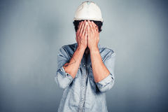 Blue collar worker covering his face. A blue collar worker wearing a hardhat is covering his face with his hands royalty free stock photos