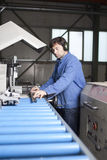 Blue collar worker in factory. Blue collar worker at machine in factory stock photos