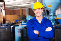 Blue collar worker. Good looking blue collar worker in factory royalty free stock images