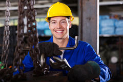 Blue collar worker. Happy blue collar worker with tools in workshop stock image
