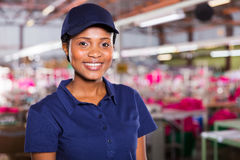 Blue collar worker. Pretty young african female blue collar worker inside clothing factory stock photos