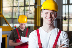 Blue-collar worker working in fabric. Smiling blue-collar worker working in fabric, horizontal royalty free stock images