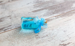Blue cologne in lying bottle Royalty Free Stock Image