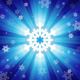 Blue color burst of light with snowflakes Stock Images