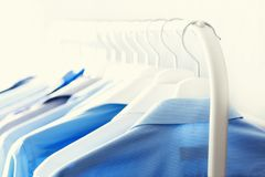 Blue color clothes. Male clothes, jackets and shirts hanging on clothes rail. Copy space. Banner.  Stock Images