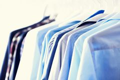 Blue color clothes. Male clothes, jackets and shirts hanging on clothes rail. Copy space. Banner.  Royalty Free Stock Photos