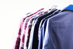 Blue color clothes. Male clothes, jackets and shirts hanging on clothes rail. Copy space. Banner.  Stock Photo