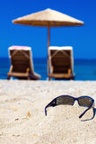 Blue color of sea and sunglasses on sand Royalty Free Stock Photos