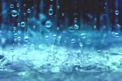 Blue color tone of close up rain water drop falling to the floor in rainy season