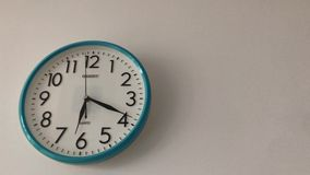 Blue color wall clock. A blue color wall clock is hanging on the wall stock video