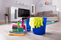 House Cleaning Products On Hardwood Floor. Blue Colored Bucket With House Cleaning Products On Hardwood Floor At Home royalty free stock photography