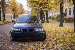Blue colored car in autumn street Stock Photos