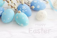 Blue colored easter eggs on the white wooden background stock photos