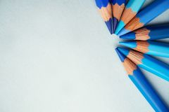 Blue colored pencils on a blue background. The blue colored pencils lying on a blue background form a semicircle stock photos