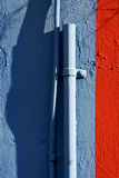 Blue colored pipe and red wall Royalty Free Stock Photo