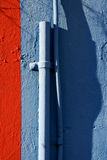 blue colored pipe and red wall Stock Images
