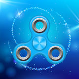 Blue colorful spinner on an abstract background with blue luminous backdrop. Abstract background with blue luminous. Backdrop. Modern children`s blue toy Stock Image
