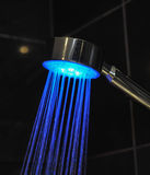 Blue coloured shower head on black tile background Stock Photography
