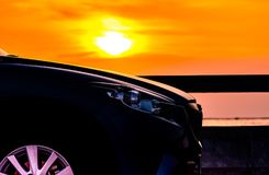 Blue compact SUV car with sport and luxury design parked on concrete road by the sea at sunset. Electric car technology stock photos