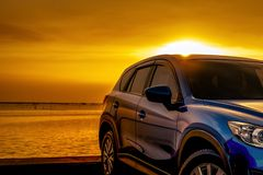 Blue compact SUV car with sport and modern design parked on concrete road by the sea at sunset. Business success concept. Road royalty free stock photo