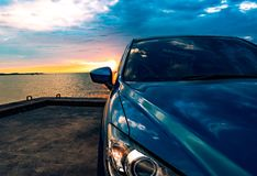 Blue compact SUV car with sport and modern design parked on concrete road by the sea at sunset. Environmentally friendly technolog Royalty Free Stock Images