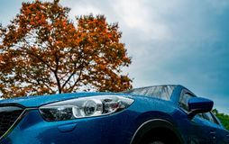 Blue compact SUV car with sport and modern design parked near red deciduous tree with blue sky and clouds. Environmentally friendly technology. Business Stock Images