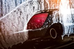 Blue compact SUV car with sport and modern design washing with soap. Car covered with white foam. Car care service business. Concept. Car wash with foam before stock image