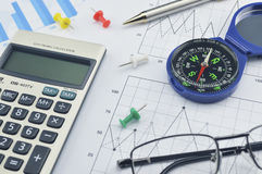 Blue compass, calculator, pen and glasses on graph paper, succes Royalty Free Stock Photo