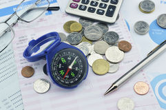 Blue compass, pen, glasses and coin on graph paper, saving conce Stock Images