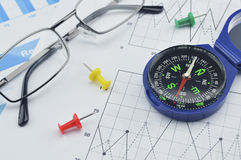 Blue compass, pin and glasses on graph paper Royalty Free Stock Photos