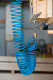 Blue compressed pneumatic air hose with pistol. Hanging at screw Stock Photo