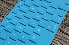Blue Computer Keyboard on Gray Wooden Surface Royalty Free Stock Images