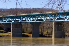 A Blue Concrete and Steel Bridge over a Brown River. Supports travel by vehicle or foot in the Midwest stock images