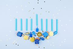 Blue confetti background with menora made of dreidels and chocolate coins. Hanukkah and judaic holiday concept. Horizontal royalty free stock photo